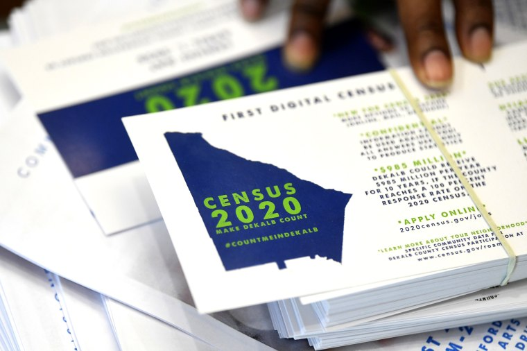 A worker gets ready to pass out instructions on how to fill out the 2020 census during a town hall meeting in Lithonia, Ga., on Aug. 13, 2019.