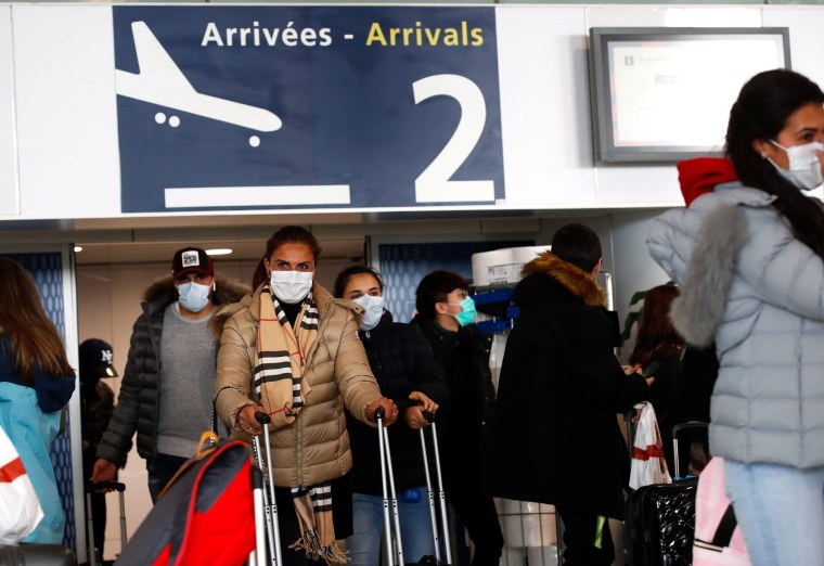 Image: People wearing protective face masks walk at as they arrive at Charles de Gaulle airport in Paris