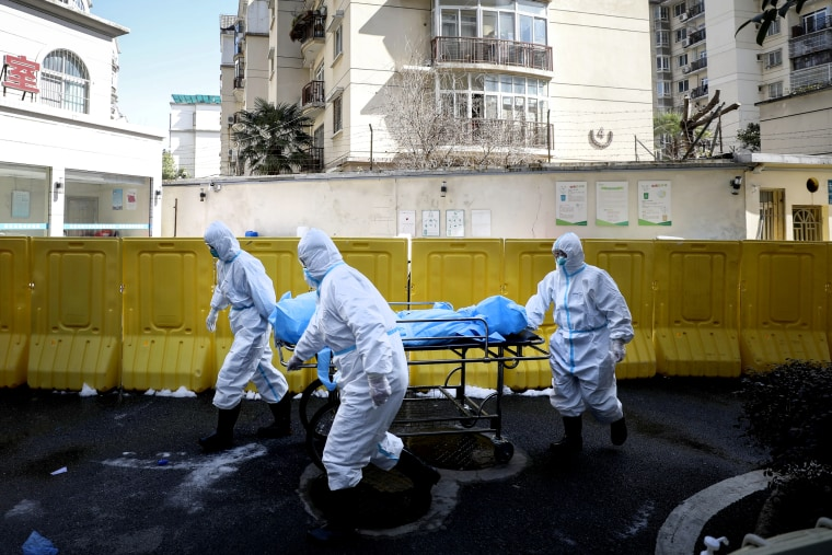 Image: Medical workers move a person who died from coronavirus at a hospital in Wuhan, China, on Feb. 16, 2020.