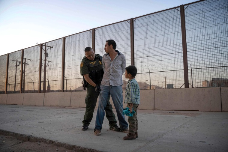 Image: Jose is searched by a Customs and Border Protection Agent as his son, Jose Daniel, looks on near the border in El Paso, Texas, on May 16, 2019.