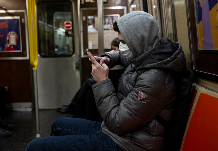 Image: A man wearing a face mask reads his phone on the subway in New York on Feb. 2, 2020.