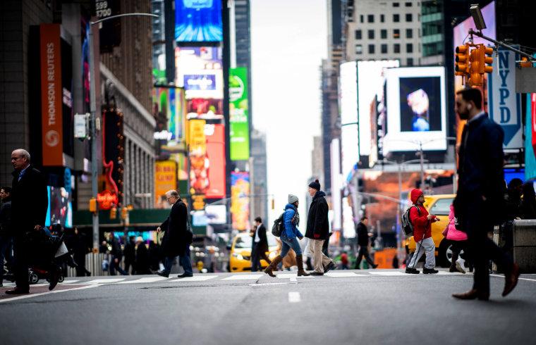 Image: People walk across 42nd Street near Times Square in New York on Jan. 14, 2020.