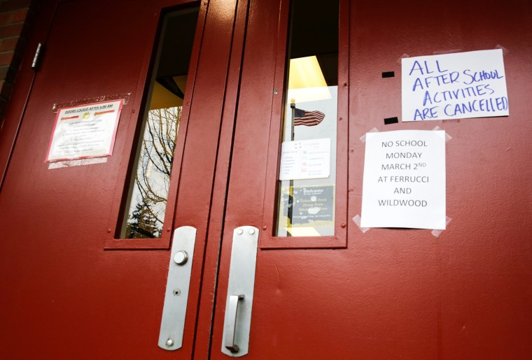Image: A US flag is reflected in a window as signs announcing a closure and cancelled activities are pictured at Ferrucci Junior High School after two schools were closed for cleaning due to flu-like symptoms of a relative in Puyallup