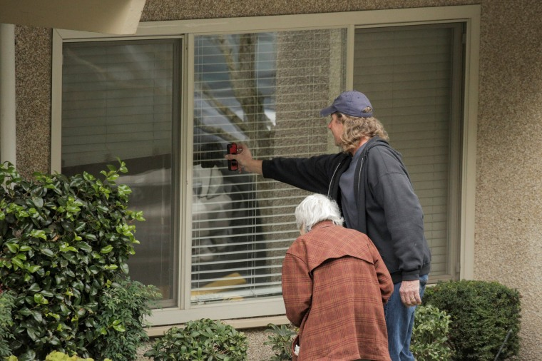 Image: Dorothy Campbell and her son, Charlie Campbell, talk through a window with her husband, Gene Campbell, at the Life Care Center of Kirkland, the long-term care facility linked to several confirmed coronavirus cases in the state, in Kirkland