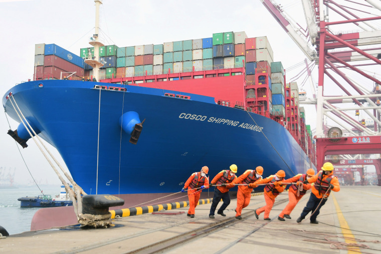 Image: Workers wearing face masks rope a container ship at a port in Qingdao