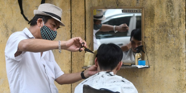 A roadside barber wearing a protective face mask amid fears of the spread of the COVID-19 novel coronavirus gives a haircut to a customer in Hanoi on February 28, 2020. - The new coronavirus has peaked in China but could still grow into a pandemic, the World Health Organization warned, as infections mushroom in other countries.