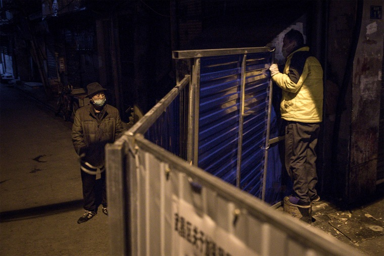 Image: Two men speak over a makeshift barricade to control the entry and exit into a residential area in Wuhan on March 4, 2020.