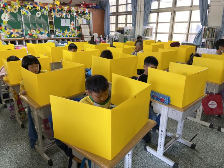 Image: Schoolchildren use plastic dividers at a school in Taiwan.