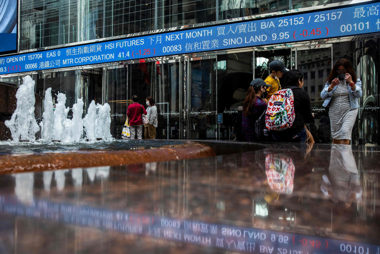 Image: A board displays stock prices in Hong Kong