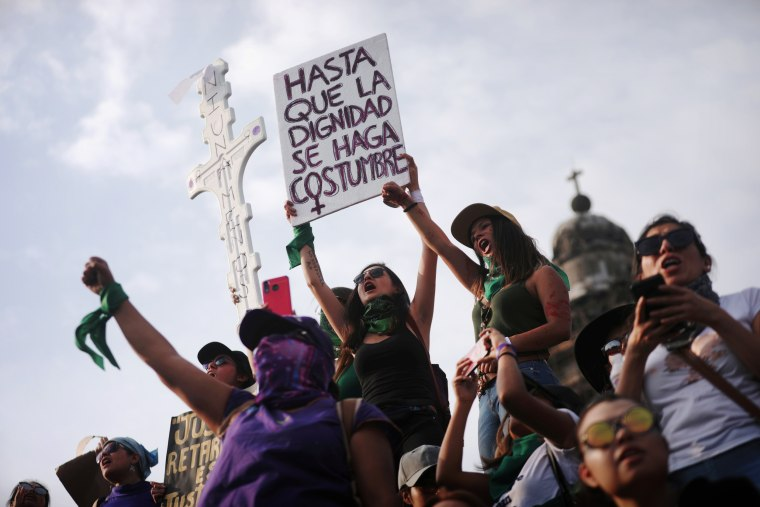 """Image: A woman holds a sign that reads \""""Until dignity becomes customary\"""" at an International Women's Day march in Mexico City on March 8, 2020."""
