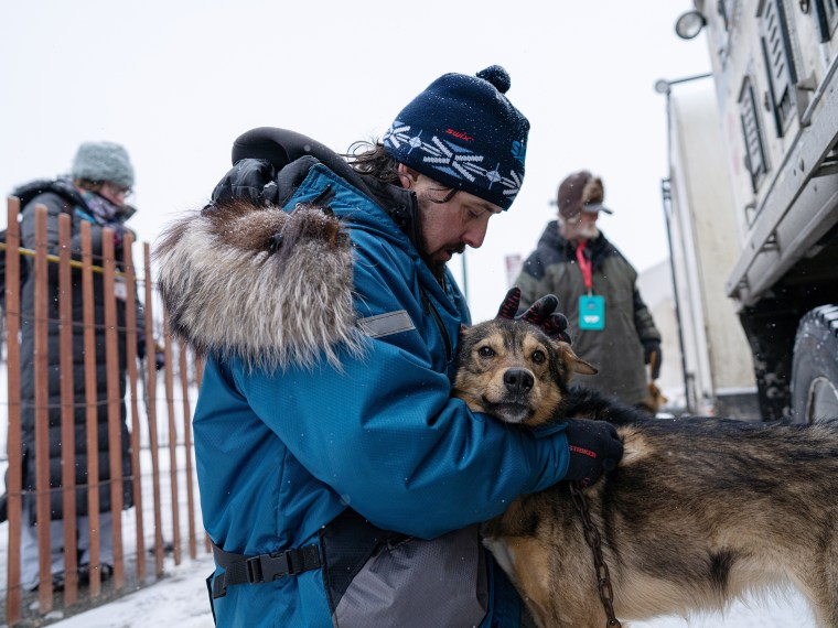 Image: Quince Mountain pets one of the dogs on his team in Anchorage on March 7, 2020.