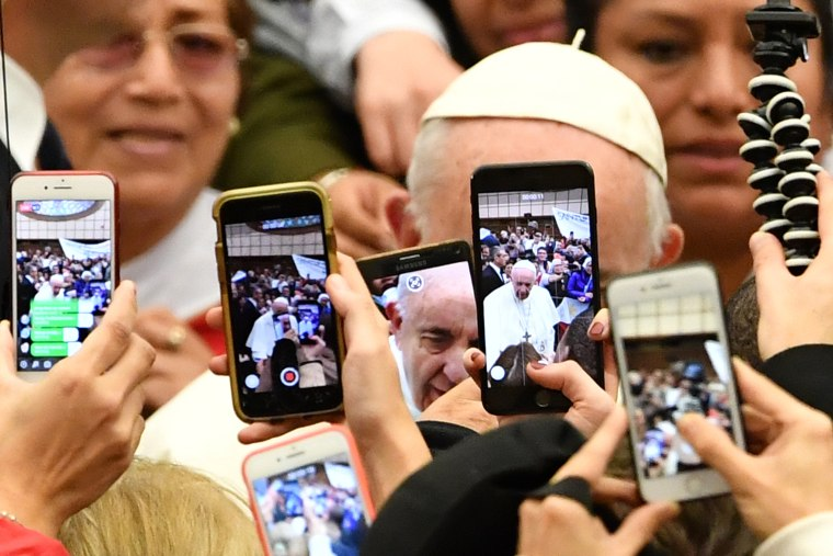 The faithful take photos of Pope Francis with their mobile phone at the Vatican