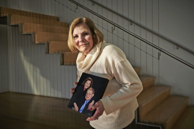 Bonnie Polin holds a photo of herself with her husband, Dr. Gerald Polin. She hasn't been able to visit him for more than a week.