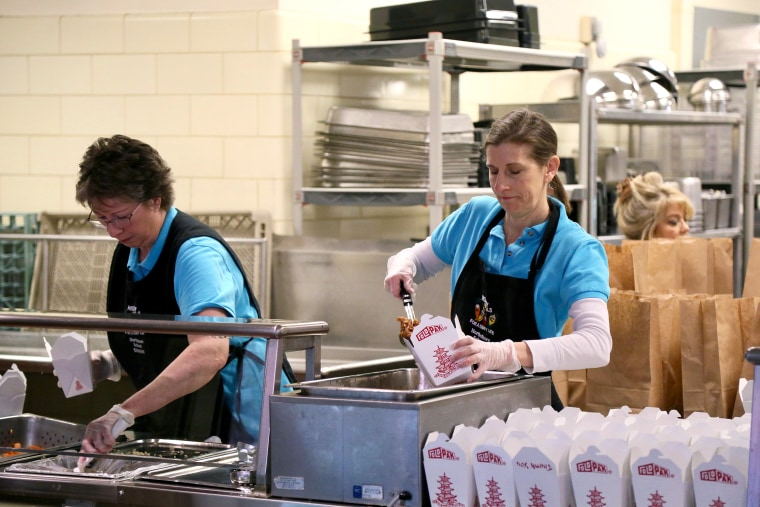 A Northshore School District cafeteria worker assembles a meal for delivery. The district went to remote learning and is offering meals for pickup at 22 school sites currently closed due to coronavirus outbreak concerns.