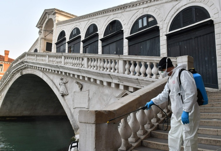 Image: An employee of the municipal company Veritas sprays disinfectant in public areas at the Rialto Bridge in Venice