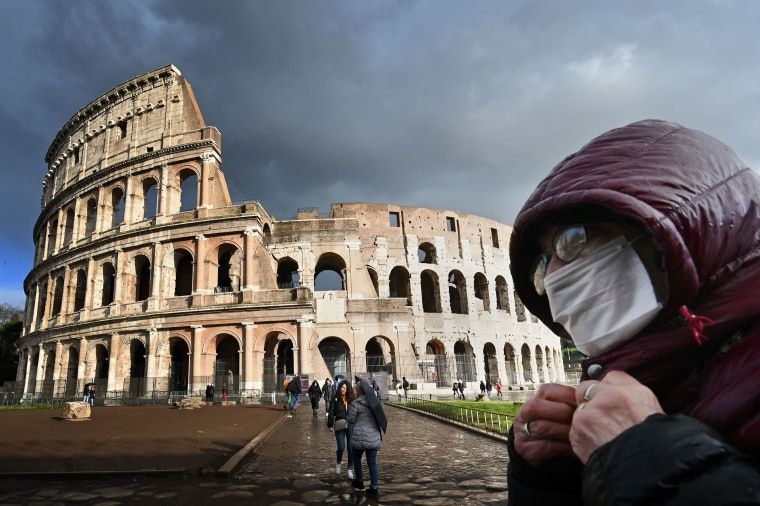 Image: A man wearing a protective mask passes by the Colosseum in Rome on March 7, 2020 amid fear of Covid-19 epidemic.