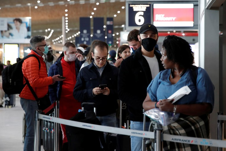 Image: People wearing protective face masks line up at the Air France ticketing desk inside Terminal 2E at Paris Charles de Gaulle airport