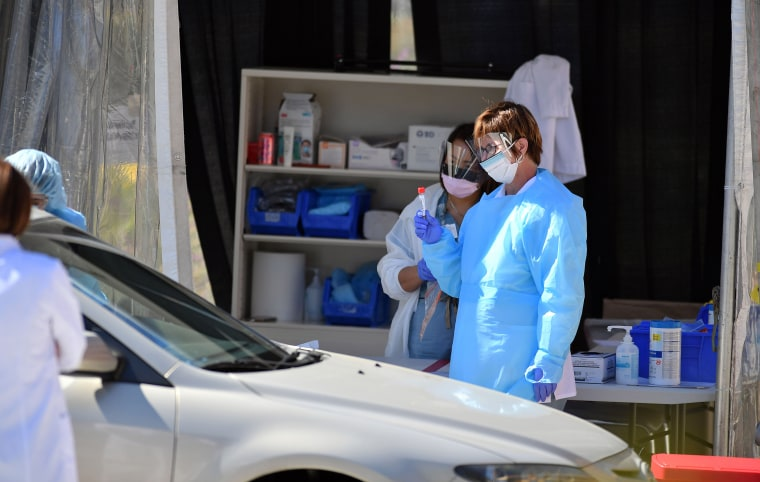 Medical workers at Kaiser Permanente French Campus test a patient for the novel coronavirus, COVID-19, at a drive-thru testing facility in San Francisco on March 12, 2020.