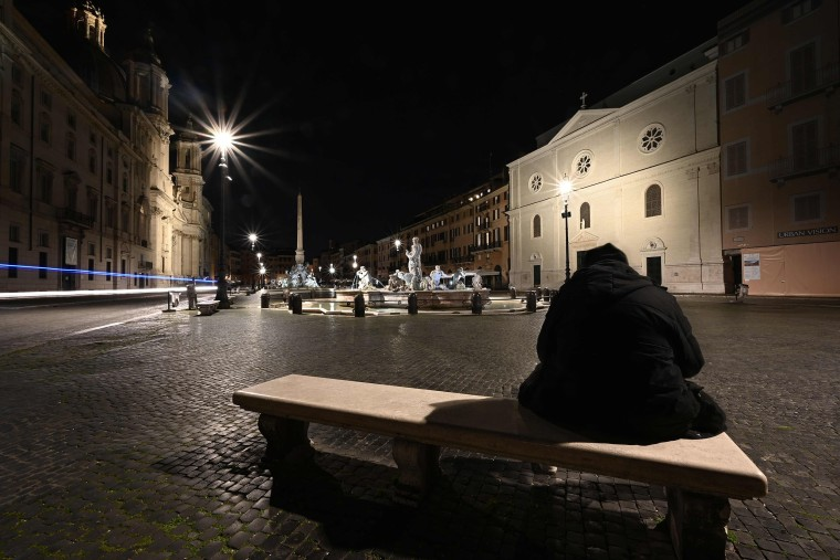Image: A man sits on a bench at a deserted Piazza Navona in central Rome