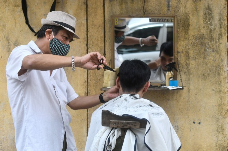 Image: A roadside barber wearing a protective face mask  gives a haircut to a customer in Hanoi