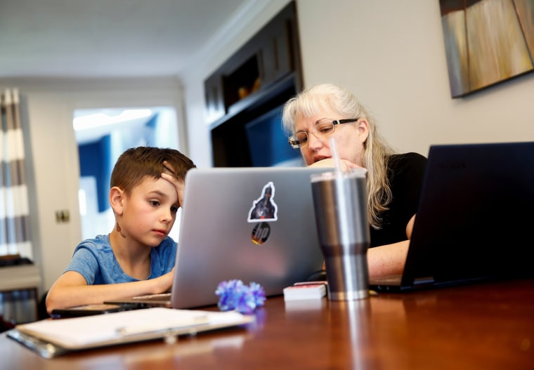 Image: Miller, a 4th grader at Cottage Lake Elementary, works with his grandmother Brackett as they try to figure out how to navigate the online learning system the Northshore School District will use for two weeks due to coronavirus concerns, at Brackett