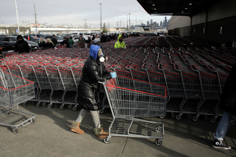 Image: Dee Jackson wears a gas mask as she and other shoppers line up before opening at a Costco store, following reports of coronavirus disease (COVID-19) cases in the country, in Seattle