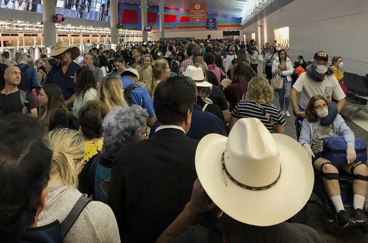 Image: People wait in line to go through customs at Dallas Fort Worth International Airport in Grapevine, Texas, on March 14, 2020.