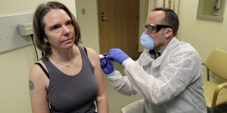 A pharmacist gives Jennifer Haller, left, the first shot in the first-stage safety study clinical trial of a potential vaccine for COVID-19, the disease caused by the new coronavirus, Monday, March 16, 2020, at the Kaiser Permanente Washington Health Research Institute in Seattle.