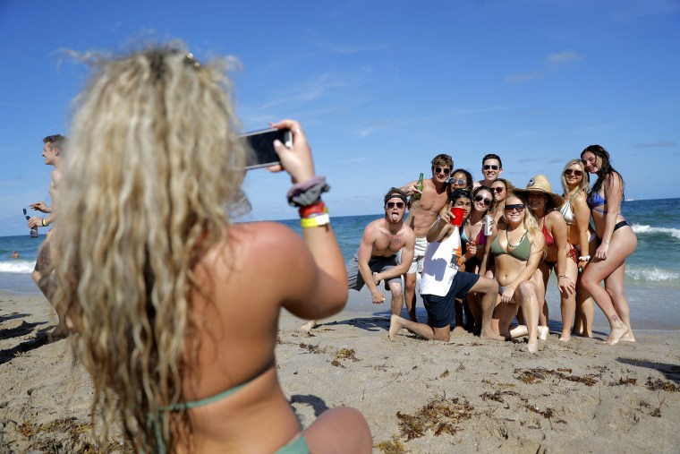 A group of spring break revelers pose for a photograph on Tuesday in Pompano Beach, Florida.