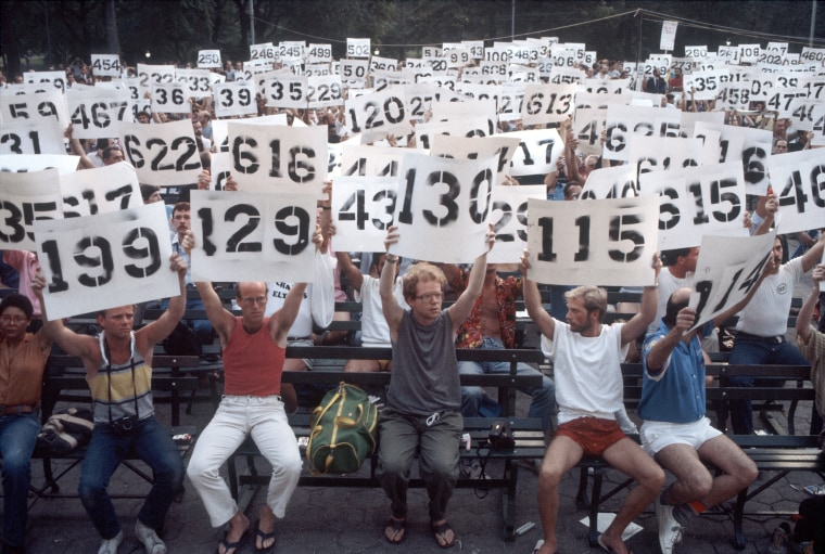People hold up signs representing the numbers of AIDS victims in a demonstration in support of AIDS victims