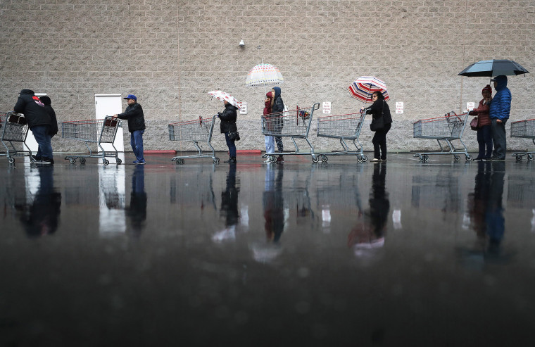Image: Shoppers wait in line in the rain to enter a Costco Wholesale store on March 14, 2020 in Glendale, California.