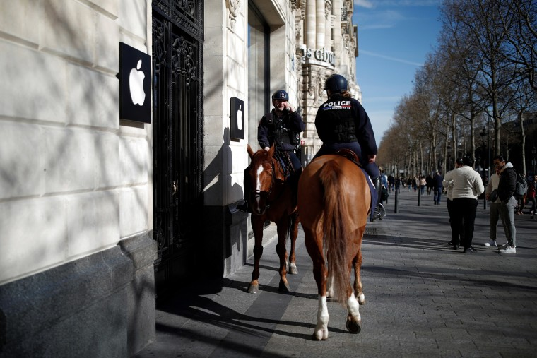 Image: Police officers on horseback patrol in front of the Apple Store on the Champs Elysees in Paris