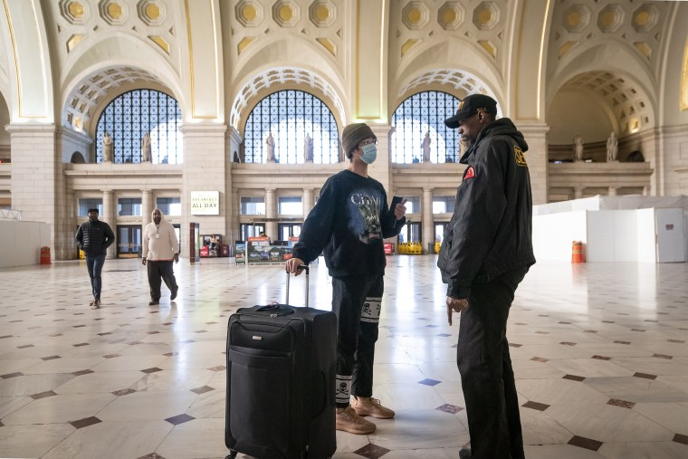 A traveler talks with a security officer at Washington Union Station, a major transportation hub in the nation's capital, on March 16, 2020.