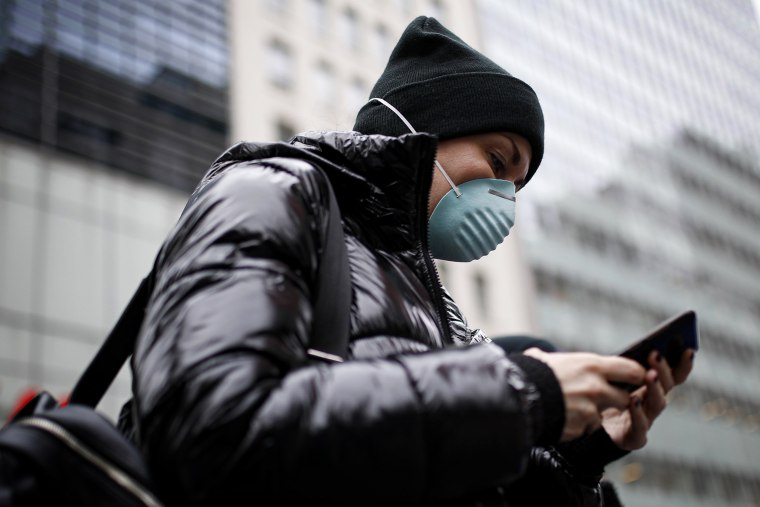 Image: A pedestrian wearing a mask reads their phone in New York on March 12, 2020.
