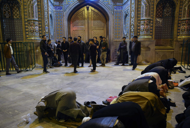 Image: People pray outside the closed doors of the Fatima Masumeh shrine in Iran's holy city of Qom