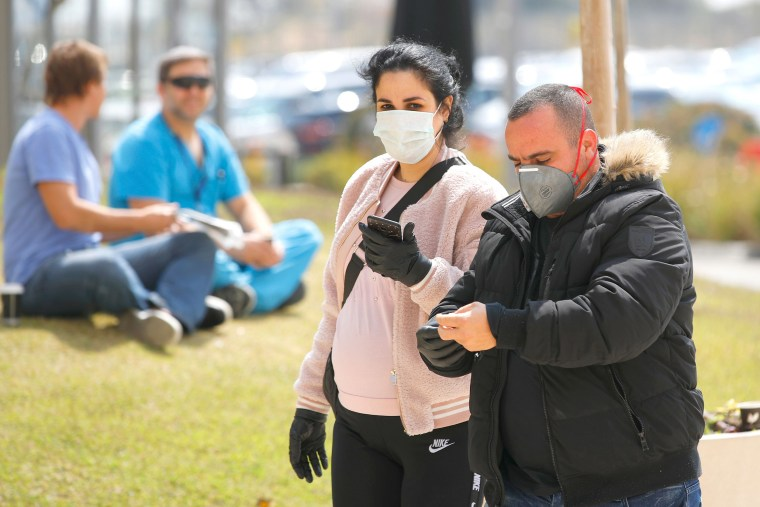 Image: People wearing protective masks walk into Samson Assuta Ashdod University Hospital on March 16, 2020 in the southern Israeli city of Ashdod, as the Jewish state introduces stringent measures to control the coronavirus pandemic.
