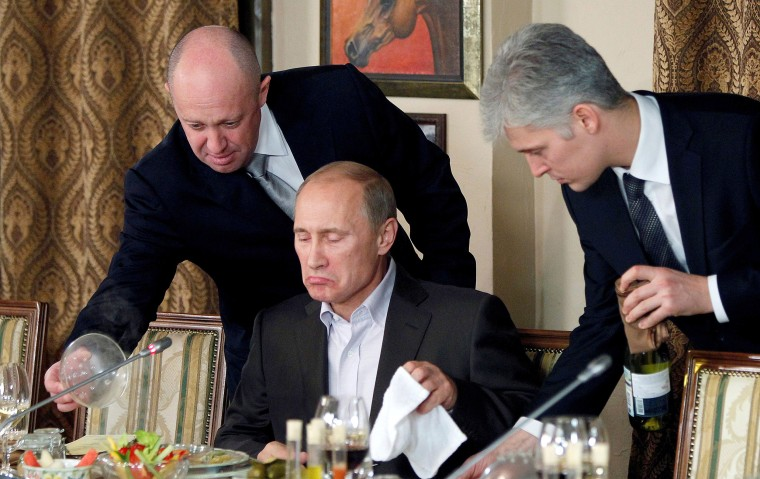 FILE PHOTO: Evgeny Prigozhin assists Russian Prime Minister Vladimir Putin during a dinner with foreign scholars and journalists at the restaurant Cheval Blanc on the premises of an equestrian complex outside Moscow