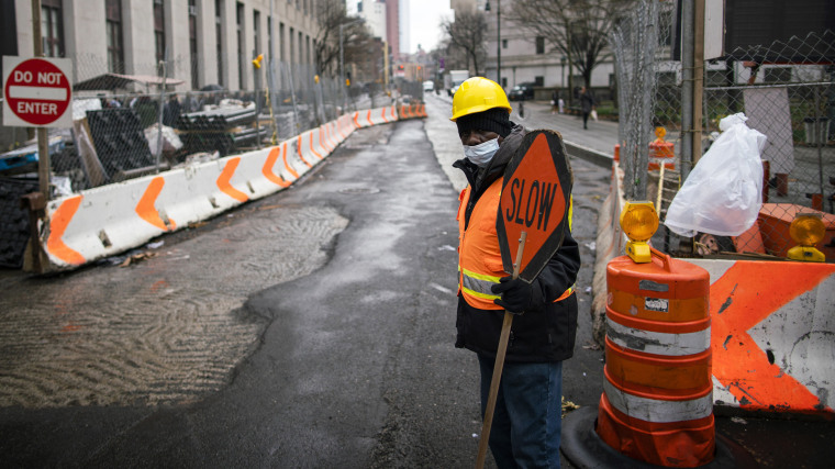 Image: A worker wearing a mask watches a road in New York on March 17, 2020.
