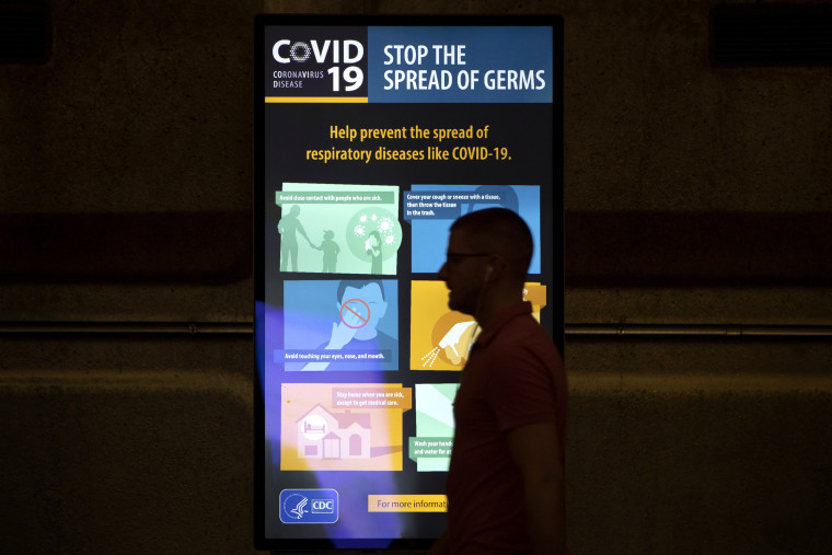 Image: A commuter walks past a CDC display of coronavirus information at the Gallery Place Metro station in Washington on March 13, 2020.