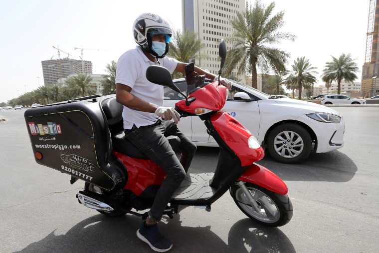 Image: A delivery man rides to deliver food, as restaurants closed, following the outbreak of coronavirus in Riyadh, Saudi Arabia.