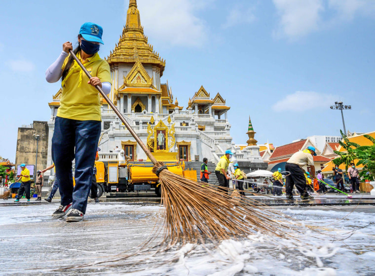 Image: Volunteers use disinfectant to clean Wat Traimit temple in Bangkok on March 18, 2020, amid concerns over the spread of coronavirus.