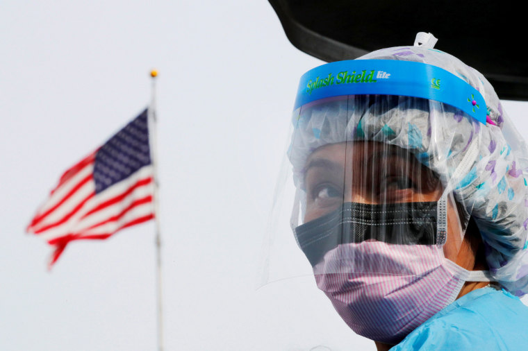 Image: A nurse wears protective gear at a drive-thru coronavirus testing site in Seattle on March 17, 2020.