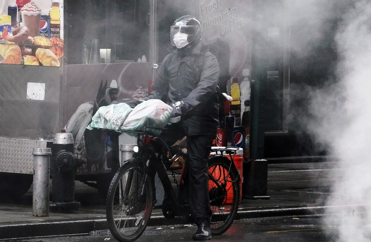Image: A delivery person on a bike rides though a steam cloud in Times Square following the outbreak of Coronavirus disease (COVID-19), in the Manhattan borough of New York City