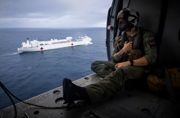 Image: A Naval aircrewman flies in a Seahawk helicopter alongside the USNS Comfort, a hospital ship, in the Pacific Ocean on on June 24, 2019.