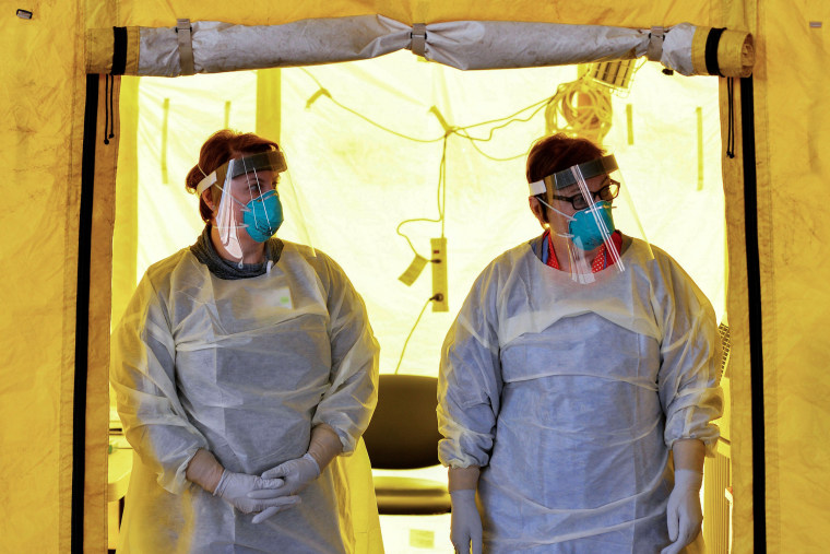 Image: Hospital clinicians wait to test patients for coronavirus at a hospital in Newton, Mass., on March 18, 2020.