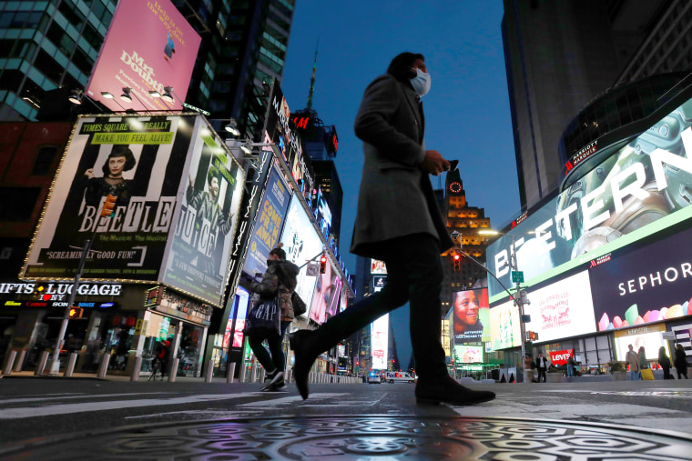 Image: People walk in Times Square as the coronavirus disease (COVID-19) outbreak continues in Manhattan, New York City