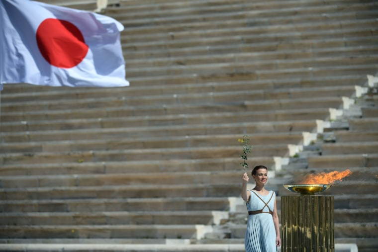 Image: A performer stands next to the Olympic flame during the Olympic flame handover ceremony for the 2020 Tokyo Summer Olympics, on March 19, 2020 in Athens.