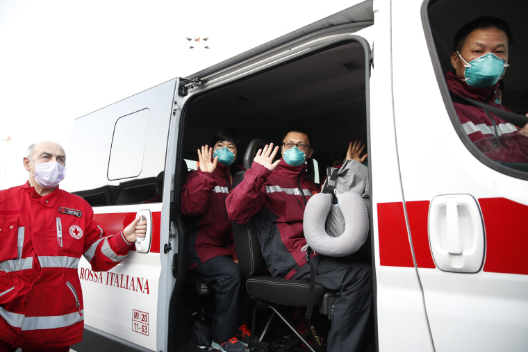 Image: Medics and paramedics from China salute as the board a Red Cross vehicle upon arrival at the Malpensa airport of Milan