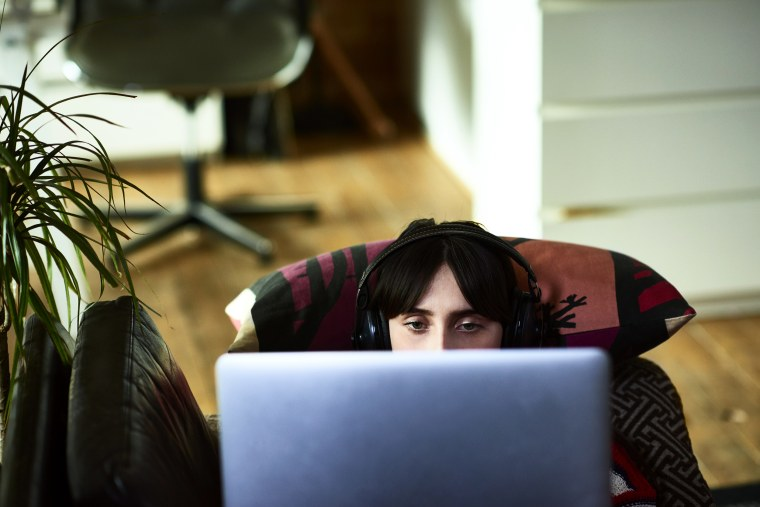 Woman using laptop and wearing headphones