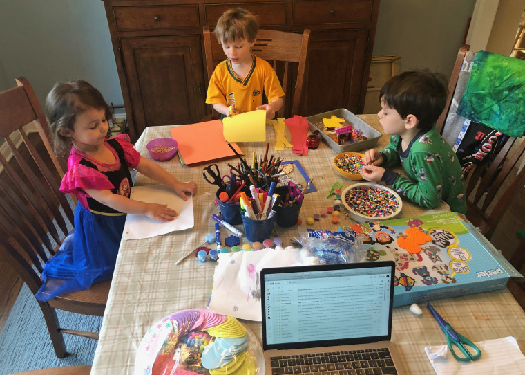Sarah McGinnity's children, Henry, 8, Clark, 5, and Lucy, 4, work on art kits purchased as the COVID-19 news got more serious.